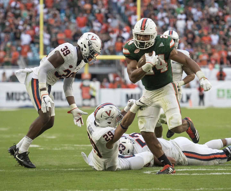 El corredor de los Miami Hurricanes Travis Homer (24) corre para un touchdown cuando el defensivo defensivo de Virginia Cavaliers Joey Blount (29) y el linebacker de Virginia Cavaliers Micah Kiser (53) se defienden durante la segunda mitad de un partido de fútbol de la NCAA el sábado 18 de noviembre de 2017 , en Miami Gardens, Florida. La Universidad de Miami derrotó a la Universidad de Virginia 44-28. (Donald Edgar / El Latino Digital)