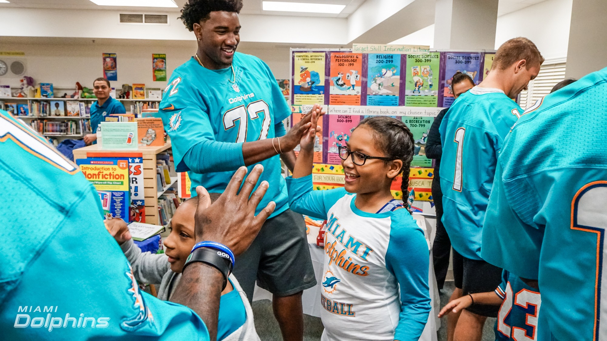T Eric Smith high fives student at Orange Brook Elementary during Back to School Backpack Event