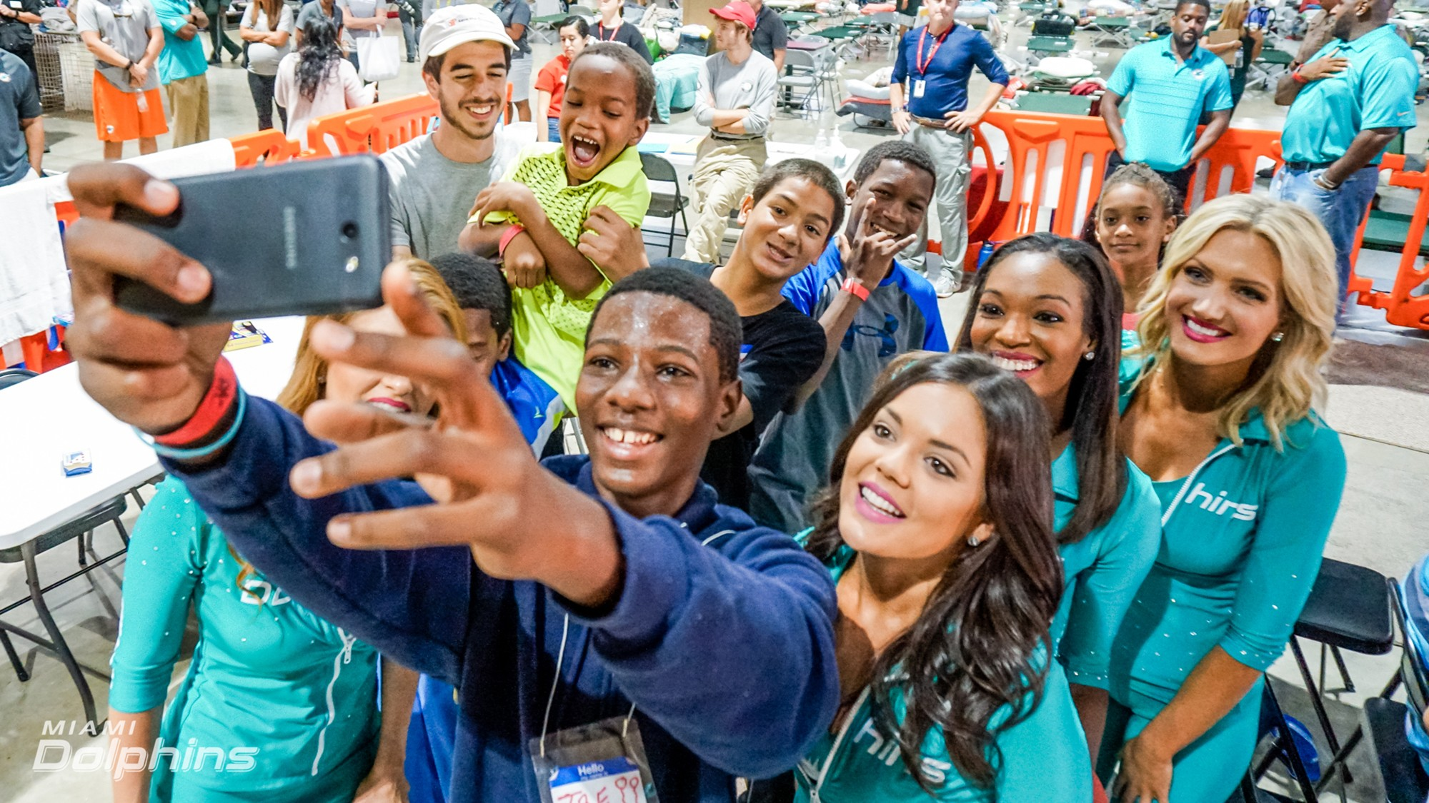 Fan takes selfie with Miami Dolphins Cheerleaders at Red Cross Shelter