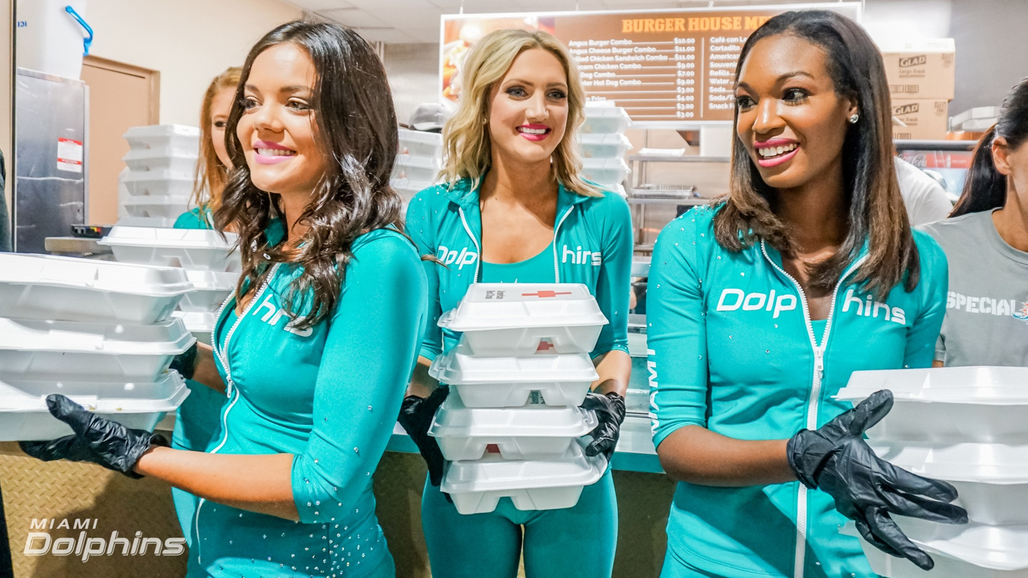 Miami Dolphins Cheerleaders (left to right) Etta, Jenny, and Jodi hand out meals at Red Cross Shelter
