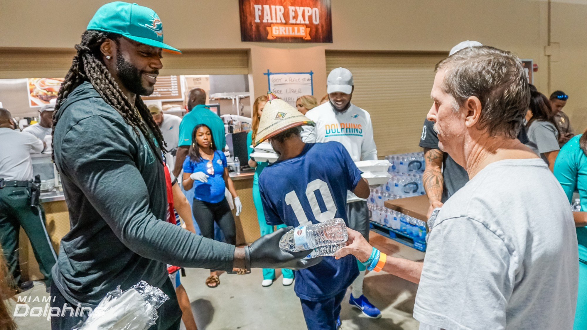 Miami Dolphins TE MarQueis Gray hands out water at Red Cross Shelter