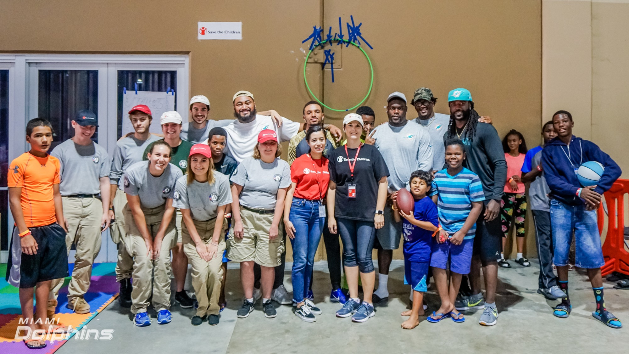 Miami Dolphins players take photo with Red Cross workers and evacuees at the Red Cross Shelter