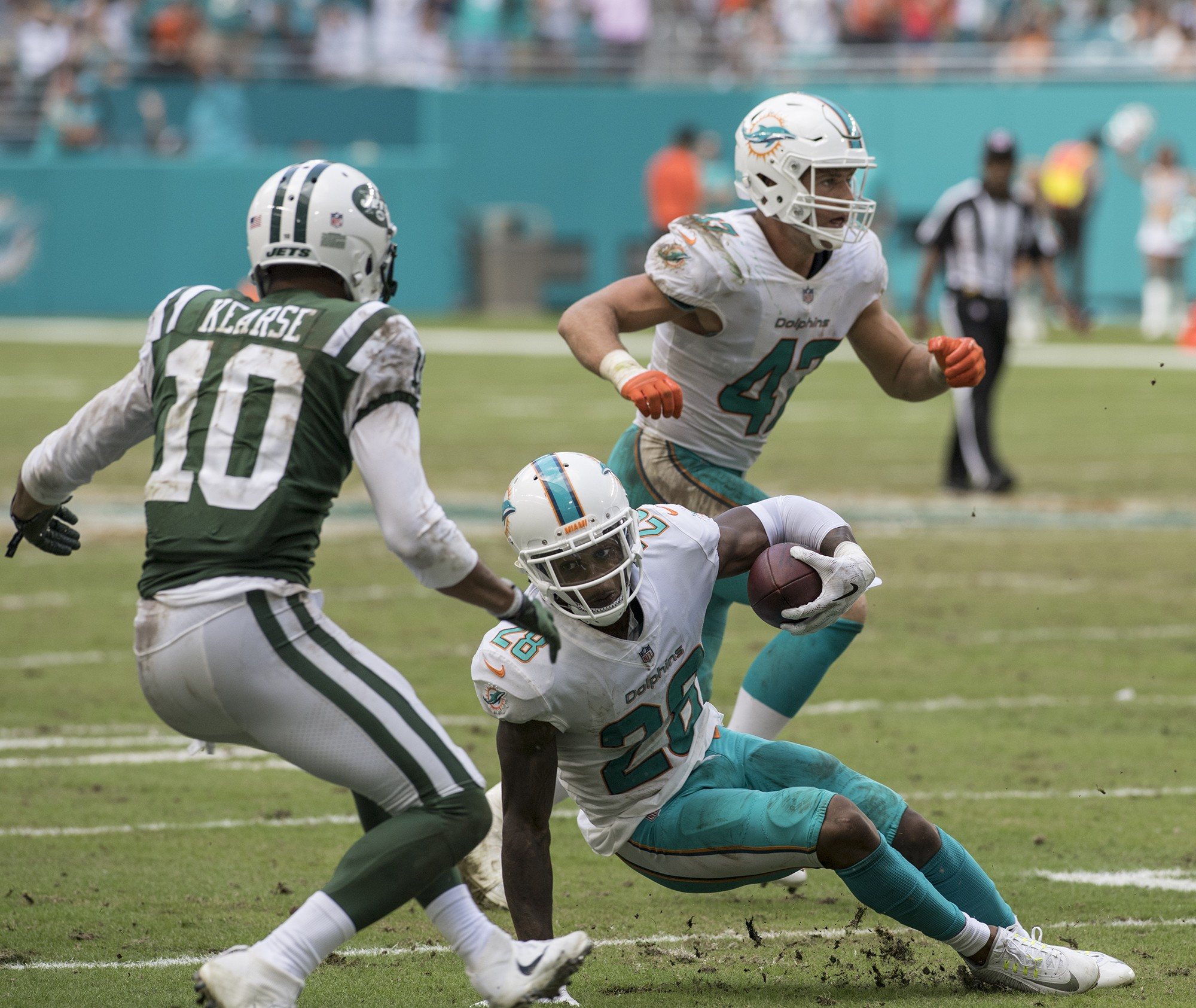 Miami Dolphins cornerback Bobby McCain (28) advance the ball after a 4th qtr interception of an NFL football game on Sunday, Oct. 22, 2017, in Miami Gardens, Fla. as New York Jets wide receiver Jermaine Kearse (10) defends. The Miami Dolphins went on to defeat the New York Jets 28-31 28-31.(Donald Edgar/El Latino Digital)