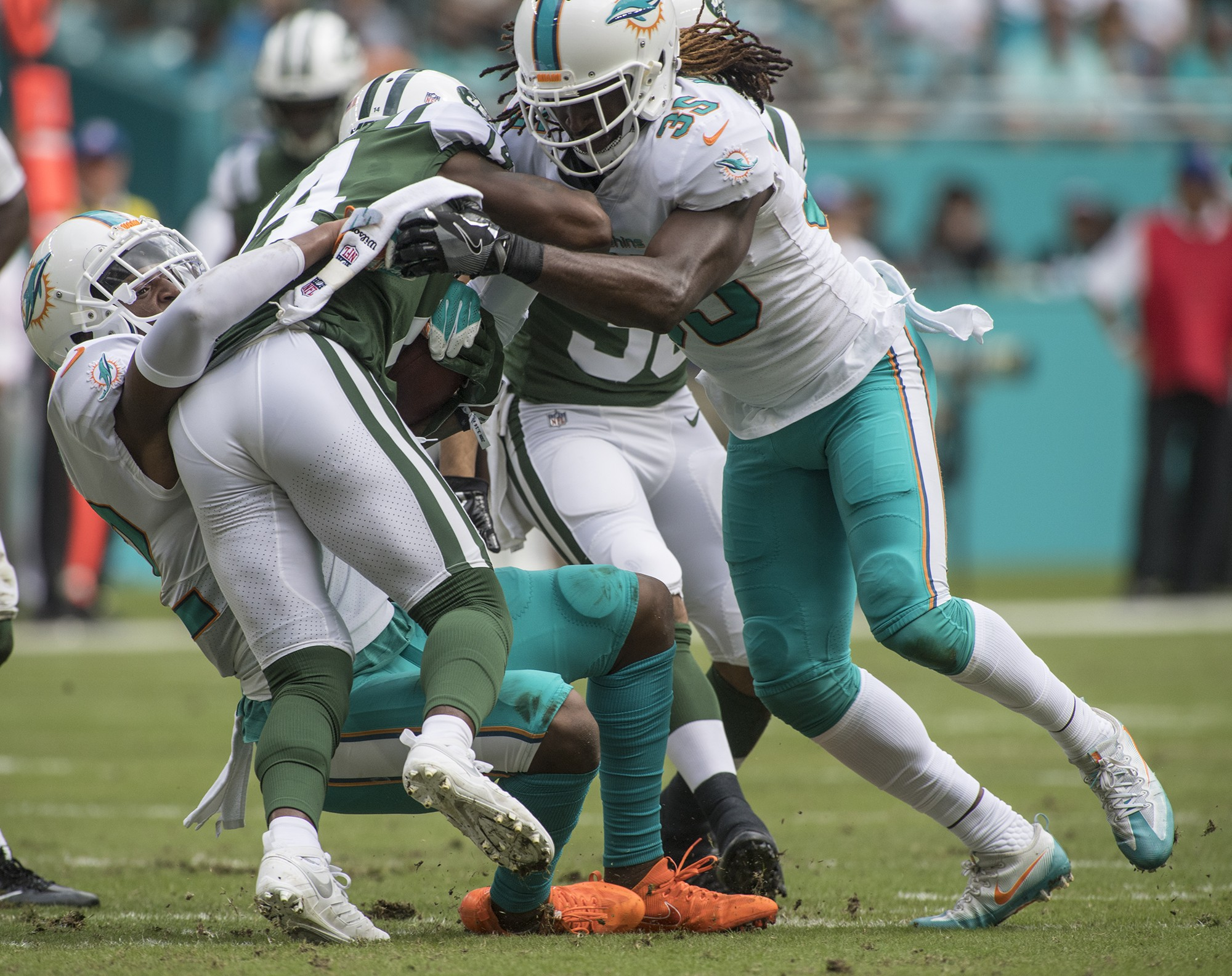 Miami Dolphins running back Kenyan Drake (32) and Miami Dolphins free safety Walt Aikens (35) bring down New York Jets wide receiver Jeremy Kerley (14) during 1st half play of an NFL football game on Sunday, Oct. 22, 2017, in Miami Gardens, Fla. The Miami Dolphins went on to defeat the New York Jets 31-28. (Donald Edgar/El Latino Digital)