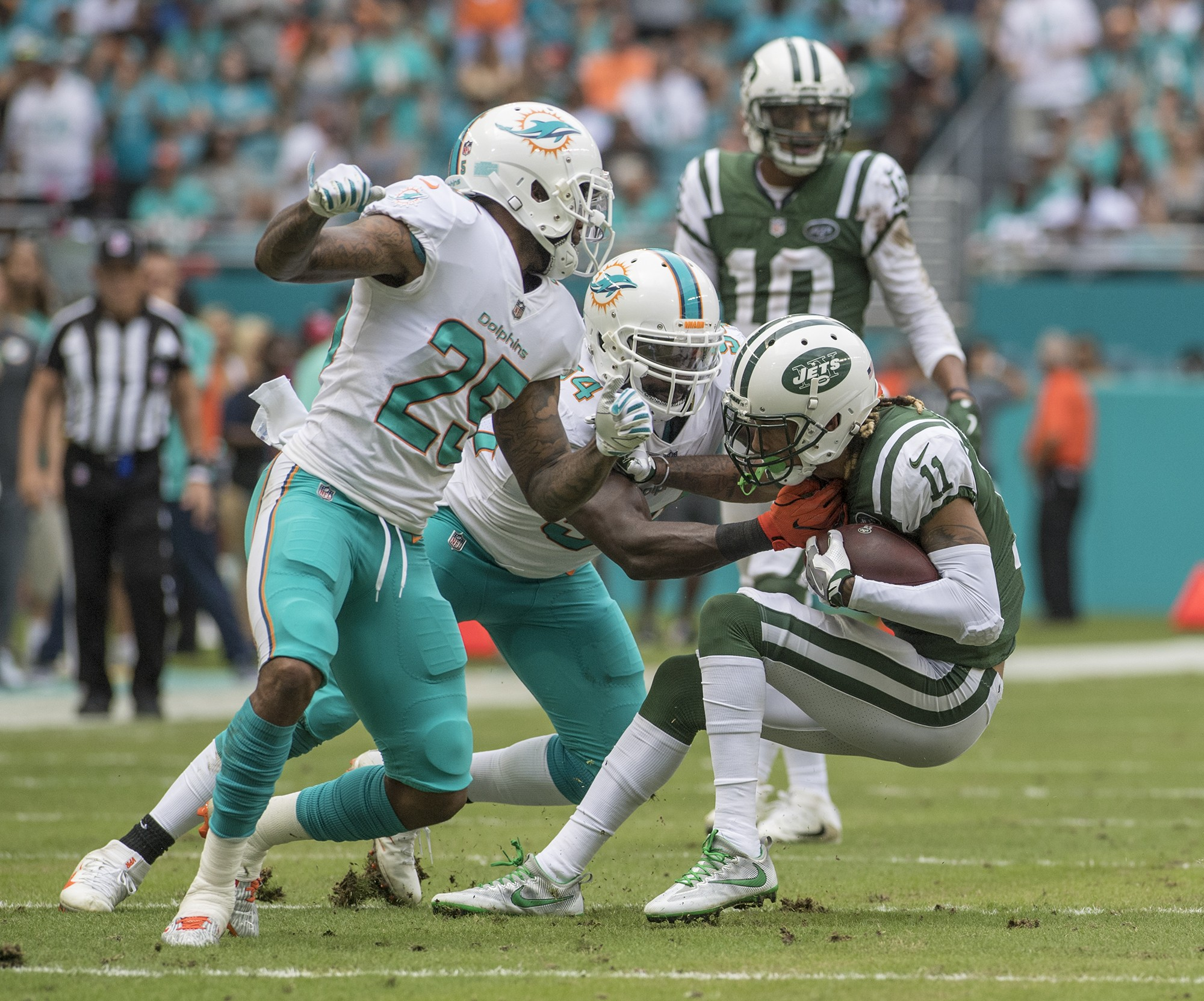 Miami Dolphins cornerback Xavien Howard (25) and Miami Dolphins outside linebacker Lawrence Timmons (94) make a stop on New York Jets wide receiver Robby Anderson (11) during 1st half play of an NFL football game on Sunday, Oct. 22, 2017, in Miami Gardens, Fla. The Miami Dolphins went on to defeat the New York Jets 31-28. (Donald Edgar/El Latino Digital)