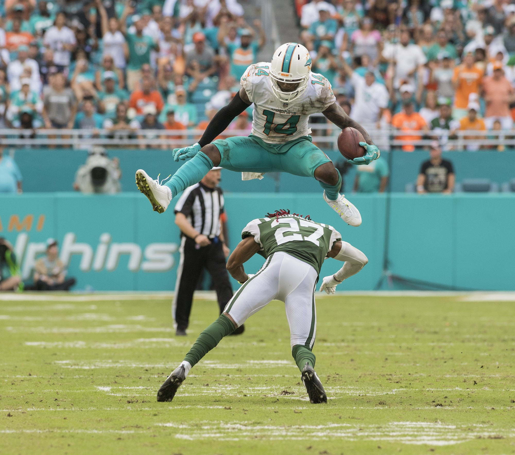 Miami Dolphins wide receiver Jarvis Landry (14) leaps over New York Jets cornerback Darryl Roberts (27) during 2nd half play of an NFL football game on Sunday, Oct. 22, 2017, in Miami Gardens, Fla. The Miami Dolphins went on to win 28-31.(Donald Edgar/El Latino Digital)