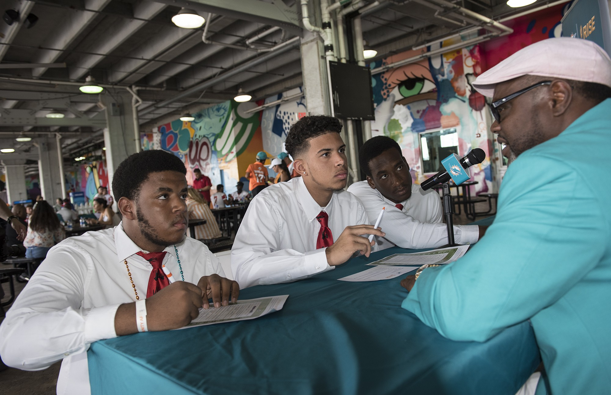 Miami Dolphins Alumni Mark Duper (1982-1992) talk with North Miami Senior High students McKlein Desaille, Ariel Soto and Stephen Pierre-Francois at the RISE tailgate party prior to the New York Jets Miami Dolphins game on Sunday, Oct. 22, 2017, in Miami Gardens, Fla. (Donald Edgar/El Latino Digital)
